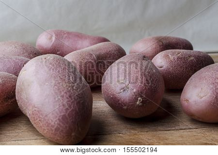 Red big imperfect potatoes on wooden cutting board