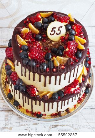 Festive two-tier cake with fruit with streaks of chocolate on a light background view from above