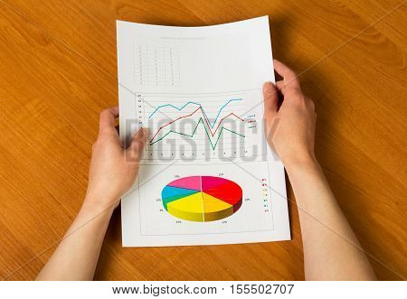 Sheet with the calculations and graphs in female hands on a background of the desktop.