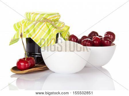 Jam jar, cup cherries and sugar, wooden spoon with berries isolated on white background