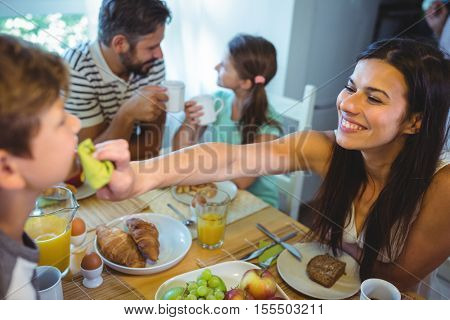 Happy woman feeding breakfast to his son at home