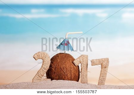Coconut instead of the number 0 in the number 2017 in the sand against the sea.