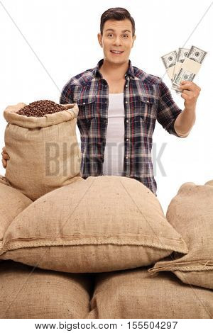 Young farmer with burlap sacks filled with coffee beans holding money bundles isolated on white background