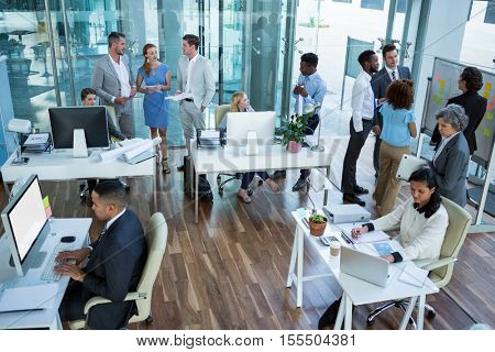 Businesspeople interacting while working in office