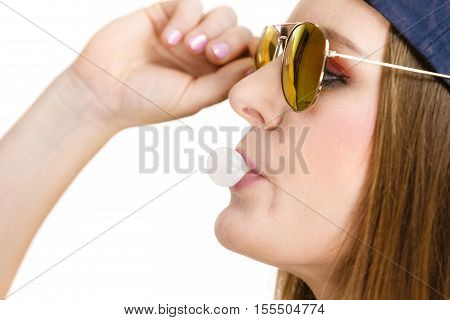 Woman casual style teen girl cap on head sunglasses doing bubble with chewing gum closeup. Youth style