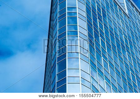 Image of modern office building against cloudy sky.