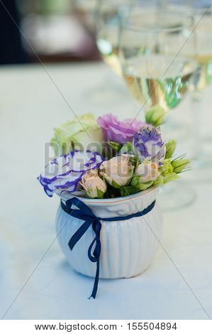 bouquet of flowers in a vase and two glasses of champagne on the table.