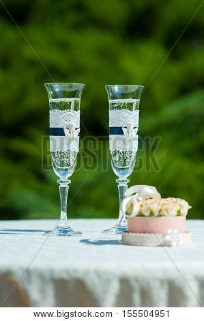 Box with wedding rings next to the glasses of champagne.