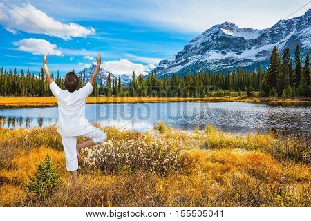 The elderly woman in a white suit for yoga. Magnificent nature of the Rocky Mountains of Canada. The concept of ecotourism