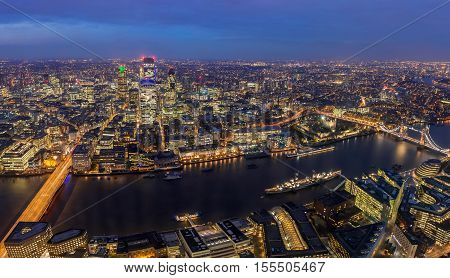 London England - Panoramic aerial skyline of London by night. This view icludes London Bridge Tower Bridge the Tower of London and famous business dristrict with skyscrapers
