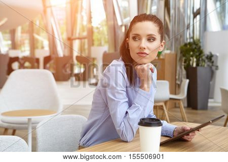 portrait of young businesswoman looking at touch pad screen while standing in modern office space interior