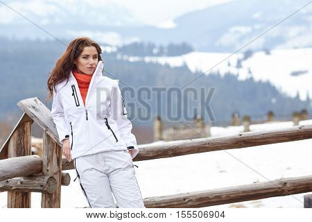 woman resting after a winter sports on the terrace of the resort house