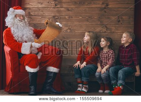 Merry Christmas and Happy Holidays. Group of three kids and Santa Claus on wooden background. Kids wait presents, Santa reads wishlist.