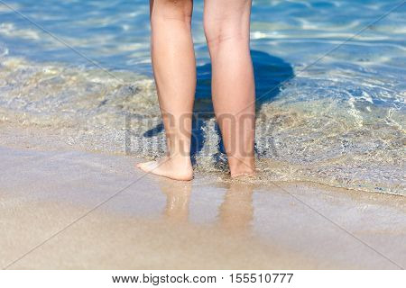 Tanned legs of sexy woman on the sandy beach