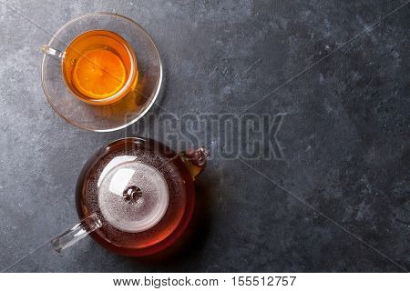 Tea cup and teapot on stone table. Top view with copy space