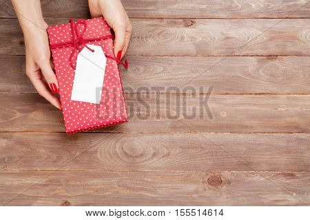 Female hands holding christmas or valentines day gift above wooden table. Top view with copy space