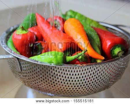 red and green pepper under running water