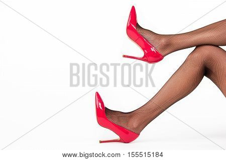 Legs in heel shoes. Red glossy footwear. Look attractive and feminine. Emphasize the beauty.