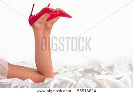Woman's legs in heels lying. Red shoes on high heel. Come play with me. Romance and temptation.