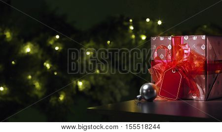 Red Christmas gift with a tree in the background wit a grey christmas ball