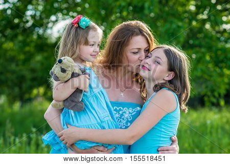 mother and two daughters in the garden