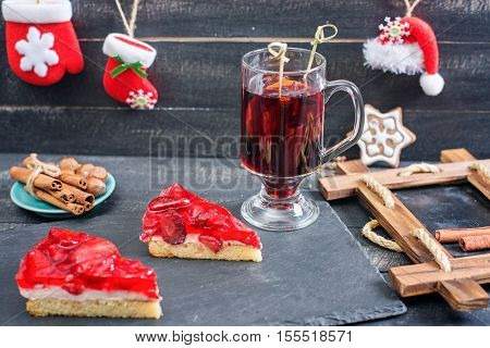 Mulled wine and strawberries cakes. Xmas style. Wooden background.