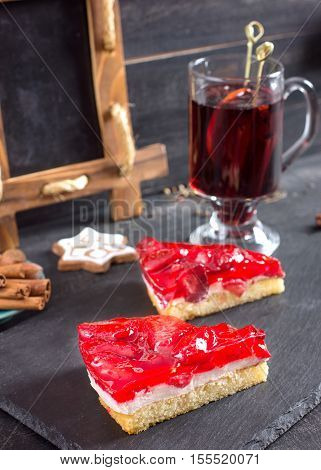 Pieces of cake with a strawberry filling and a souffle and Mulled wine cinnamon sticks and christmas cookies for decoration.