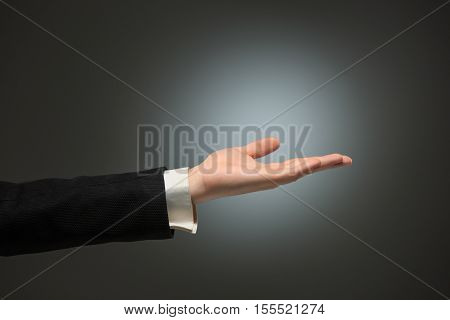 Dressed in a business suit caucasian male hand gesture of asking for the help or showing anything over the dark background
