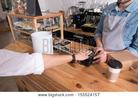 Comfortable payment. Close up of womans hand using terminal while young waiter standing behind the bar and working