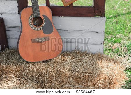 Guitar on straw in wall home background with copy space.