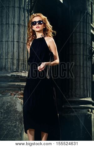 Beautiful blonde woman in long black dress and sunglasses in the city center. Fashion model outdoor.