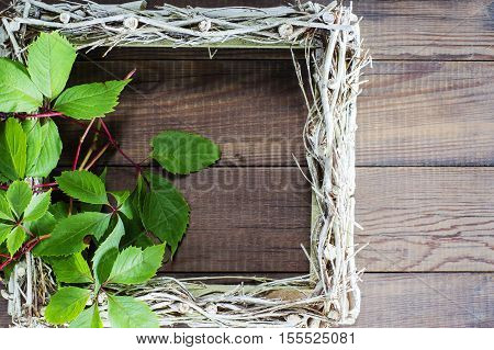 Empty picture frame decorated wild grapes. Wicker frame on the cover of wine barrel.