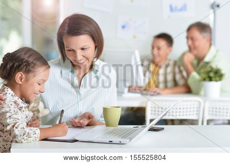 Young mother helping her cute little daughter do homework