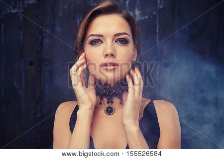 Close-up portrait of beautiful sensual woman with elegant hairstyle. Perfect make-up. Eveningwear with jewelry