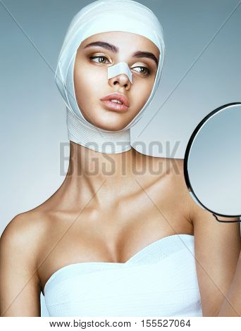 Beauty victim with bandage on her face after facelift. Photo of perfect girl after plastic surgery looking in mirror. Beauty concept