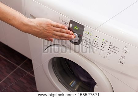 Young woman or housekeeper has a laundry day at home she select the program