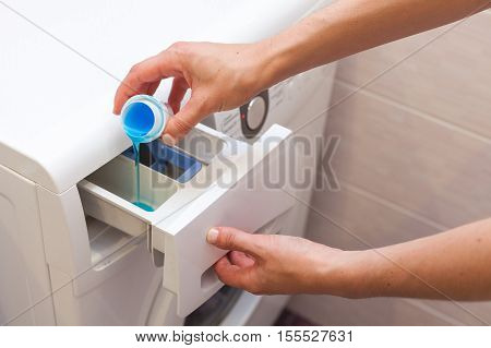 Woman pours the liquid powder in washing machine