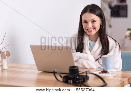 Delightful lifestyle. Lovely charming young woman relaxing and having a coffee while using her laptop in a cafe.