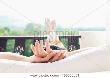 Rear view of asian woman relaxing on a sofa and looking outside a green background view at home terrace. Relaxing concept.