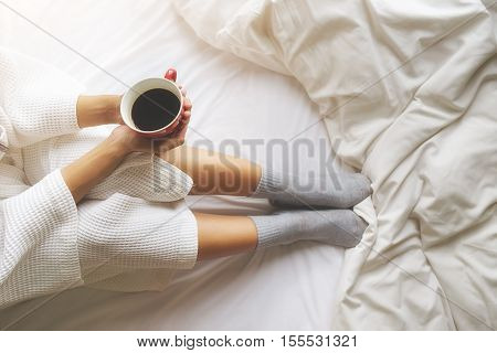 Beautiful asian woman hand holding a cup of coffee on the bed with morning light. Relaxing concept. Retro filter effectsoft focusselective focus.