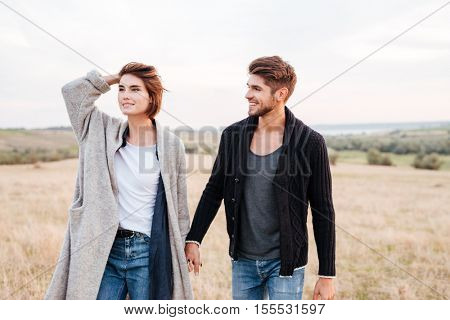 Happy smiling young couple enjoying walk through the grass field