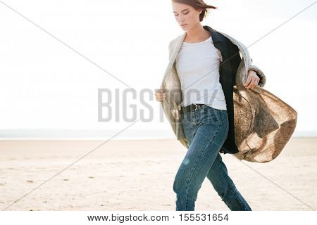 Cropped image of a beautiful casual woman walking on the seashore in sunlight