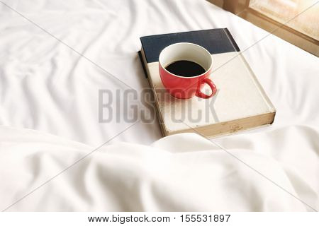 A cup of coffee on book with copy space. Morning with a book. Relaxing concept. Retro filter effectsoft focusselective focus.
