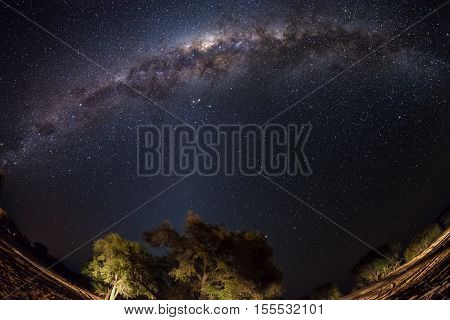 Starry sky and Milky Way arc with details of its bright colorful core captured with fisheye lens from the Namib desert in Namibia Africa. Adventures into the wild.