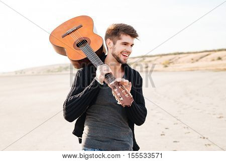 Portrait of a young casual smiling man walking at the beach and holding guitar on his shoulder