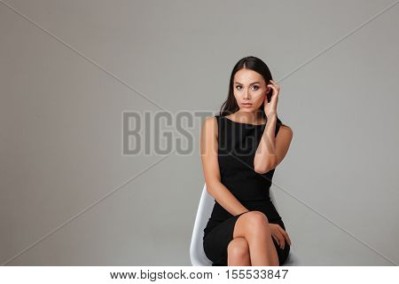 Full length portrait of a beautiful pensive brunette woman with long hair and black dress over gray background