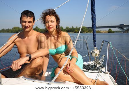 Happy couple sails on yacht on river with bridge at sunny summer day