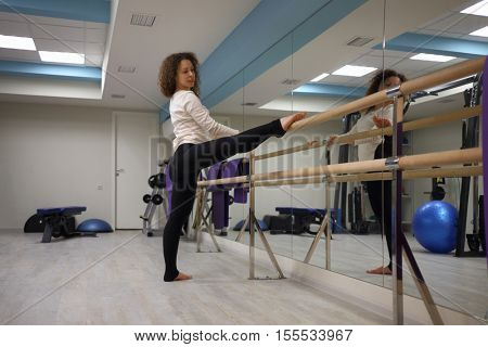 Woman does stretching exercises on ballet bar in gym with fitness equipment and mirror