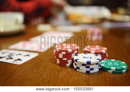 Casino chips, playing cards on table, cup, hands out of focus