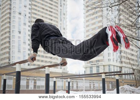 Man does exercises on parallel bars on sport playground in yard at winter, back view